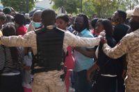 Haitisk polis försöker hindra folk att ta sig till USA:s ambassad i huvudstaden Port-au-Prince på fredagen.