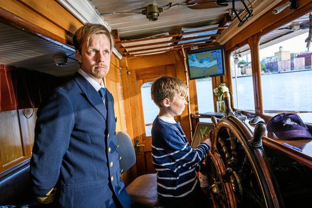 Olof styr ångbåten Blidösund från kommandobryggan. Erik håller koll på att allt går bra.