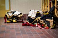 Brandstation med brandmäns skyddskläder förberedda för utryckning. Arkivbild.