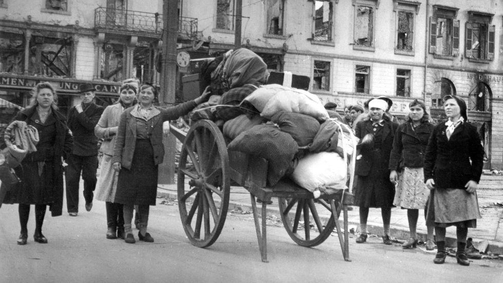 Tyska flyktingar anländer till Karlsruhe på sin väg västerut, 1945. På vagnen har de samlat allt de äger.
