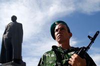 Här poserar en prorysk separatist i Ukrainska staden Luhansk vid ett monument över den röde terrorns ledare, Felix Dzerzhinsky.