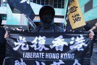 """En demokratiaktivist i Hongkong håller upp en banderoll med texten """"Befria Hongkong""""."""