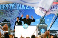 Yviga gester av premiärminister Berlusconi vid ett valmöte i Milano i oktober.