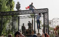 Tunisiska soldater vaktar huvudentrén till parlamentsbyggnaden i Tunis medan demonstranter samlas utanför.
