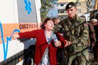 En soldat som kallats in tar hand om en kvinna intill en raserad byggnad efter jordbävningen som uppmätte 6,4 på Richterskalan.