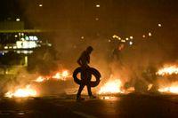 Demonstranter bränner däck i samband med upploppet i Malmö i slutet av augusti.