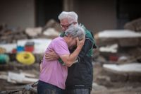 Ett brödrapar gråter i varandras armar framför föräldrahemmet som förstörts i vattenmassorna i tyska Altenahr.
