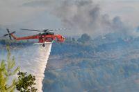 Elden vattenbombas vid Olympia, de olympiska spelens vagga, i västra Grekland.