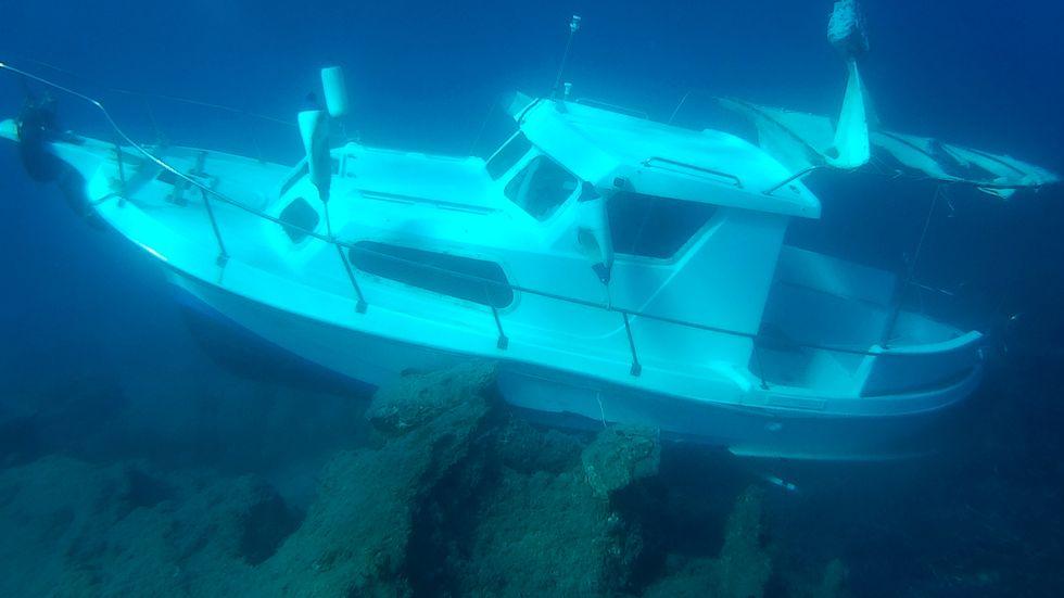 Instängda i den här båten drunknade sex barn och två kvinnor natten till söndagen bara 25 meter från stranden på Samos. Bilden togs efter att grekiska dykare förgäves försökt rädda de nödställda.