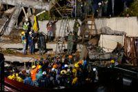 Räddningspersonal letar efter en person som fastnat under rasmassorna i resterna av den kollapsade grundskolan Enrique Rebsamen.