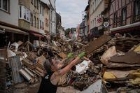 En kvinna slänger skräp i Bad Neuenahr-Ahrweiler i västra Tyskland, efter de översvämningar som skakat landet.