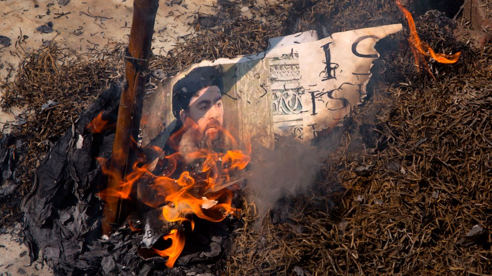 Bild på al-Baghdadi brinner under en protest.