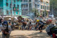 Beväpnade styrkor beskjuter demonstranter med tårgas när de samlats i staden Rangoon i mars. Våldet får nu Sverige att lägga om sitt bistånd. Arkivbild.