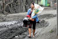 Leila de Castro går bland asktäckta hus i sydöstra Filippinerna. I famnen bär hon en stor staty av Jesusbarnet som hon räddade från sin systers hus när de evakuerade.