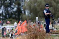 Polis bevakar en begravningsplats i Christchurch efter fredagens terrordåd.