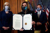 Nancy Pelosi, talman i USA:s representanthus, visar upp det påskrivna riksrättsåtalet mot president Donald Trump, vilket representanthuset röstade igenom tidigare i veckan.