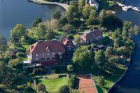 Flygbild över villor med sjötomt på en udde i Djursholm.