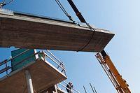 Bärande tak och väggar reses av byggarbetare från Skanska vid bygge i Gåshaga.