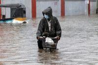 En man försöker att cykla över en översvämmad gata i Chennai i Tamil Nadu i Indien.