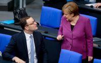 Tysklands förbundskansler Angela Merkel i samtal med Jens Spahn tidigare i veckan. Nu erbjuds Merkelkritikern en plats i hennes tilltänkta regering.