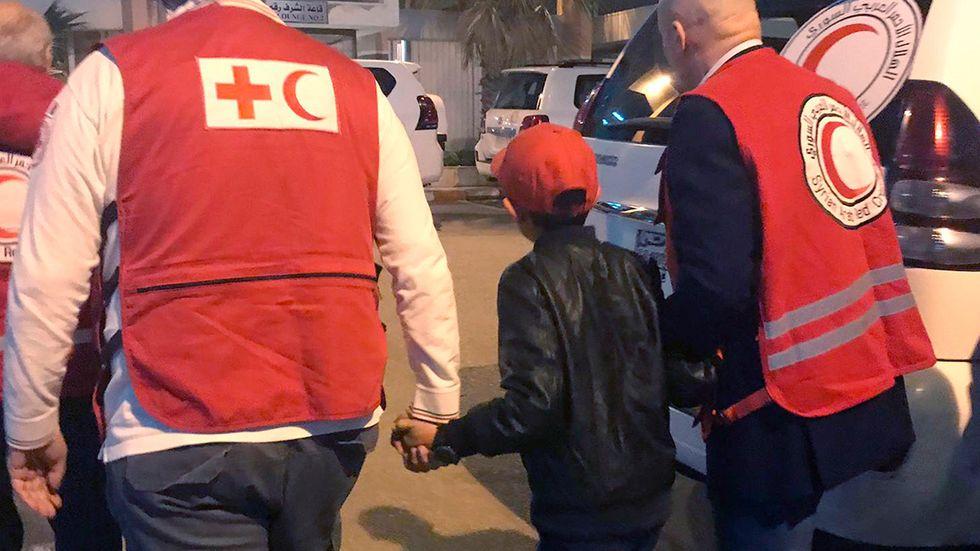 Hjälparbetare tar med en 11-årig pojke från lägret al-Hol i Syrien den 6 november. Pojken flögs till Italien där han har anhöriga.