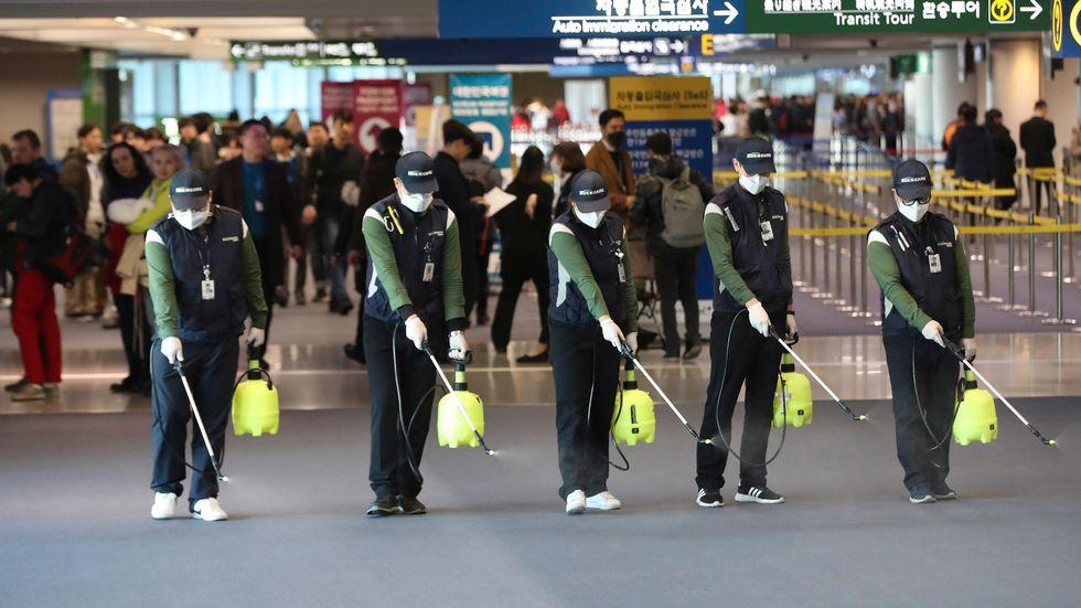 Corona-konsekvens. Arbetare impregnerar ankomsthallen på den internationella flygplatsen i koreanska Incheon med antiseptisk lösning.