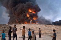 Färre svenskar reser till Syrien och Irak för att slåss med terrorgrupperingar, men ett hundratal finns redan på plats, enligt Säpo. Bilden visar en brinnande oljekälla några mil utanför Mosul i Irak.