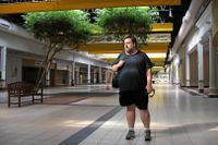 """En öde korridor med mörka fasader, järngrindar och dörrar täckta av spånplattor i köpcentret Glen Burnie Plaza i delstaten Maryland i USA. Här finns fortfarande några öppna butiker. """"Vitaminbutiken GNC är alltid de sista som stänger. Även efter ett atomkrig kommer de att hålla öppet, det är jag säker på"""", säger filmaren Dan Bell som dokumenterar köpcentrens nedgång."""