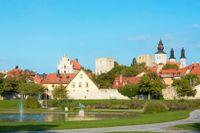 Almedalen i Visby, hustak och torn från ruiner och domkyrkan, byggnader från 1200-talet som trappgavelhuset gamla apoteket bredvid nyare hus, gammalt och nytt, Gotland.