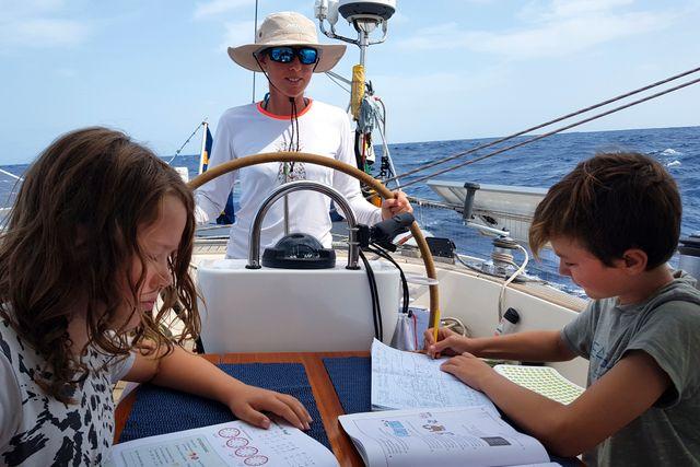 Hampus och brorsan Helmer gör skolarbete ombord medan mamma Cecilia styr båten Indian Summer.