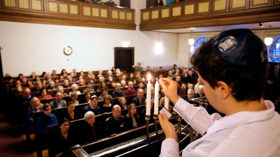 Tre ljus tänds under judiska församlings minnesstund i Malmö synagoga i samband med Förintelsens minnesdag 2013.