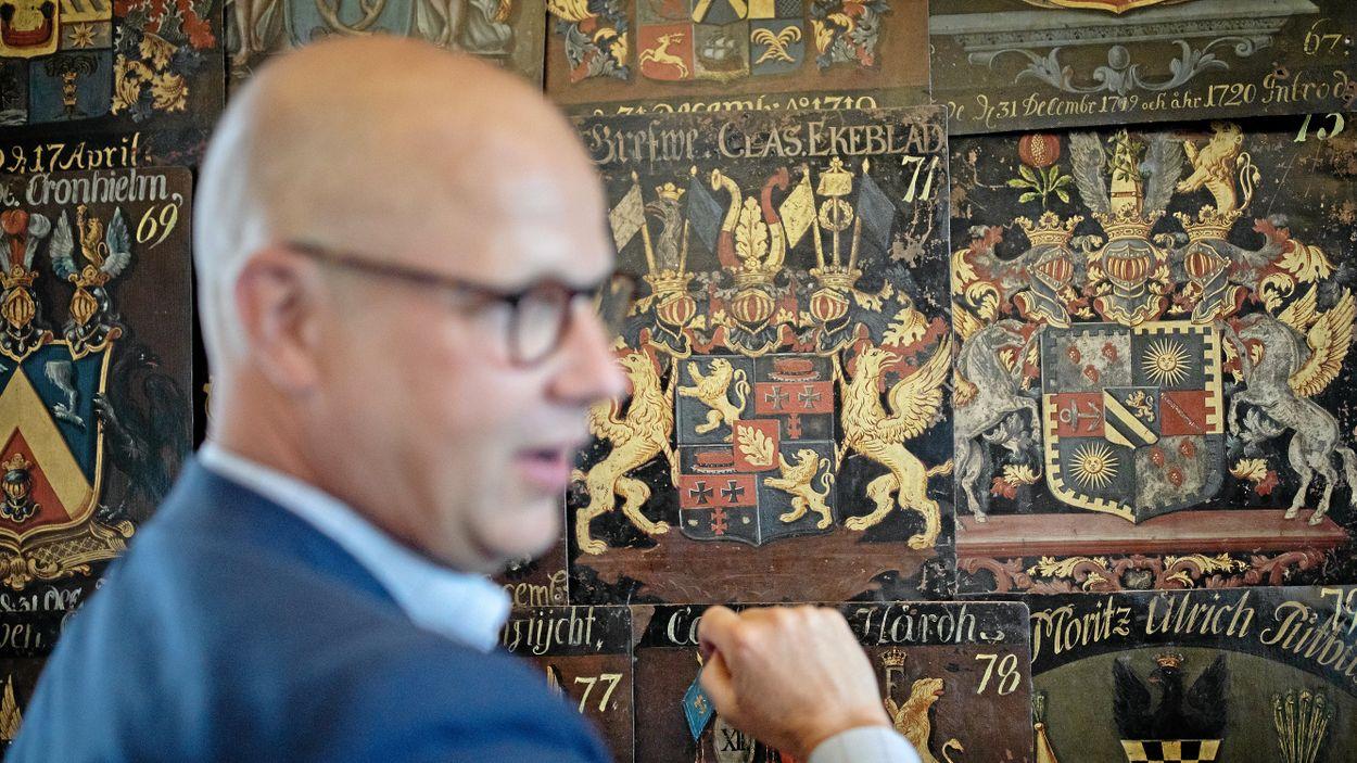 Riddarhuschefen Erik Drakenberg poserar vid sin ätts vapensköld i Riddarsalen.