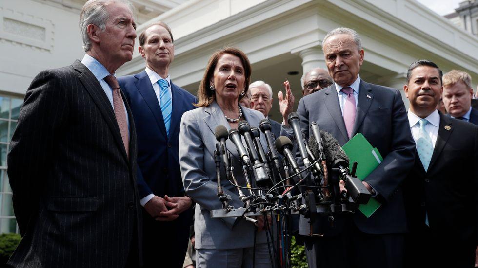 Demokraternas kongressledare Nancy Pelosi och Chuck Schumer, omgivna av partikamrater, uttalar sig för medierna efter tisdagens möte med president Donald Trump i Vita huset.