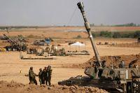 I Netivot, nära gärnsen mot Gaza, rengör israelsika soldatern pipan på en artillerienhet.