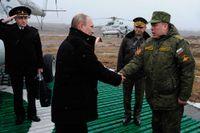 Rysslands president Vladimir Putin skakar hand med befälhavaren för det västra området i närheten av S: t Petersburg. Ryska trupper har haft en stor övning.