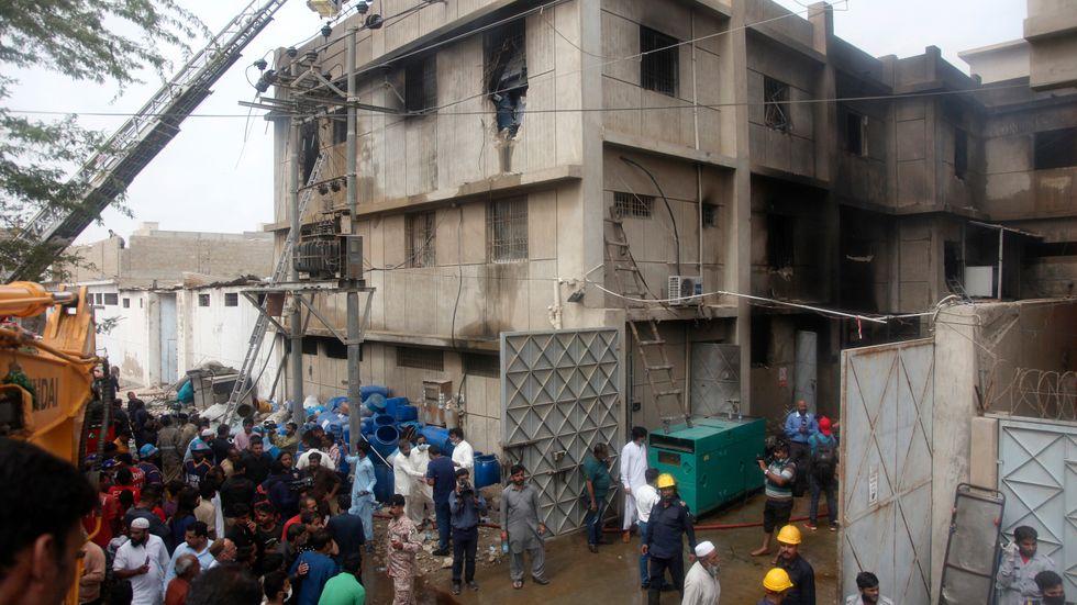 Räddningsinsatser pågår för att söka igenom fabriken i Karachi som drabbades av en brand under fredagen. Arkivbild.