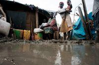 Achol Onak utanför den plats där hon och familjen bott under snart tre månader. Tidigare sov de ute på marken men nu med regnen går det inte längre. Även inne kommer regnvattnet och svämmar över golvet. Barnen sover i en säng samtidigt som Achol sover sittandes. Hennes make sover inte alls då det inte finns något annat utrymme att sitta eller ligga på.