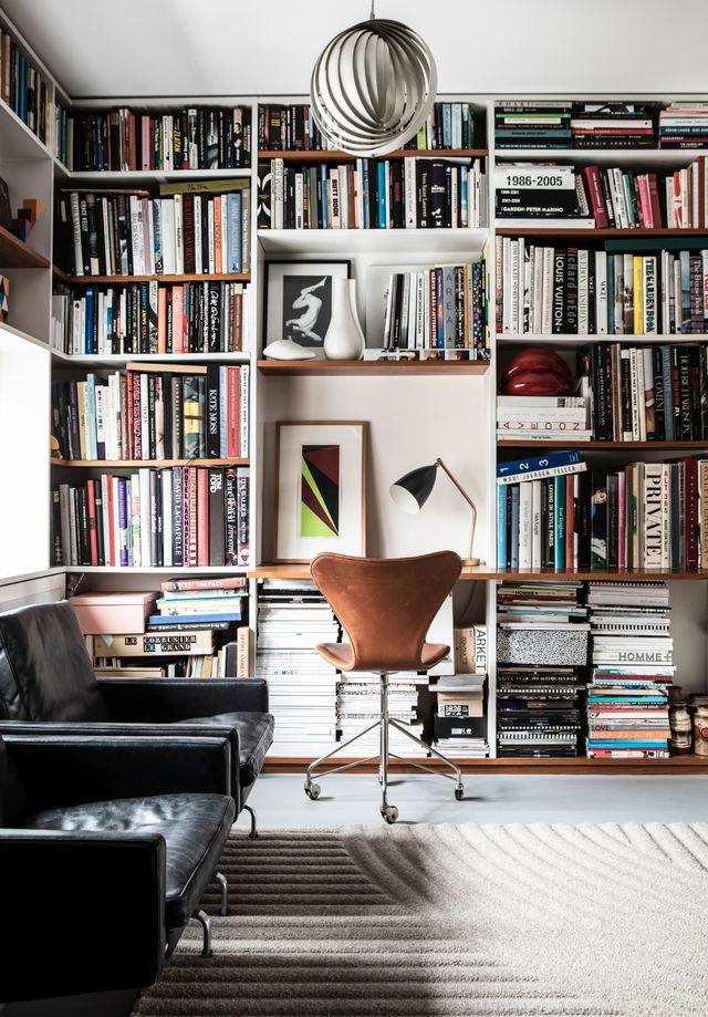 Den platsbyggda bokhyllan i husets kontorsdel är skapad av Thomas Eriksson arkitekter. Skrivbordsstol, Arne Jacobsen. Matta, Ogeborg.