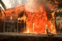 Ett hus slukas av lågorna i den våldsamma Woolseybranden i Malibu, Kalifornien, den 9 november.
