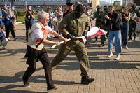 En polis försöker rycka den vit-röd-vita oppositionsflaggan ur 73-åriga Nina Bahinskaja händer underprotester i Minsk i Belarus på lördagen. Bahinskaja uppges sedan ha gripits.