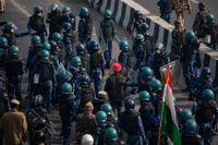 En protesterande jordbrukare släpps av kravallpolis under tisdagens protester. Arkivbild.
