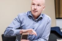 Fingerprint Cards vd Christian Fredrikson tillsammans med en telefon med företagets fingeravtrycksavläsare.