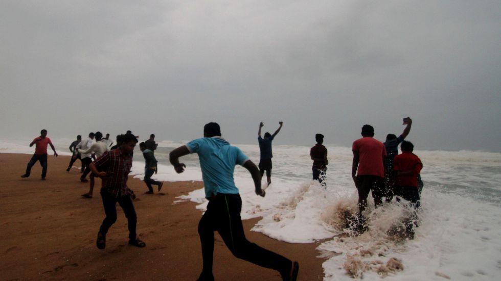 Personer springer undan tidvattnet på en strand i Puri, i delstaten Odisha.