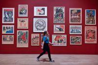 """En besökare framför några av de propagandaaffischer som visas på utställningen """"Red star over Russia"""" på Tate Modern i London."""