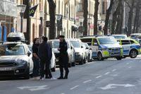 Poliser och avspärrningar på den plats på Birger Jarlsgatan där en skottlossning ägde rum under fredagen.