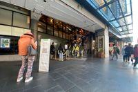 En kvinna checkar in med hjälp av mobiltelefonen och QR-kod vid köpcentret Broadway Shopping Center i Sydney, där flera smittade personer befunnit sig.