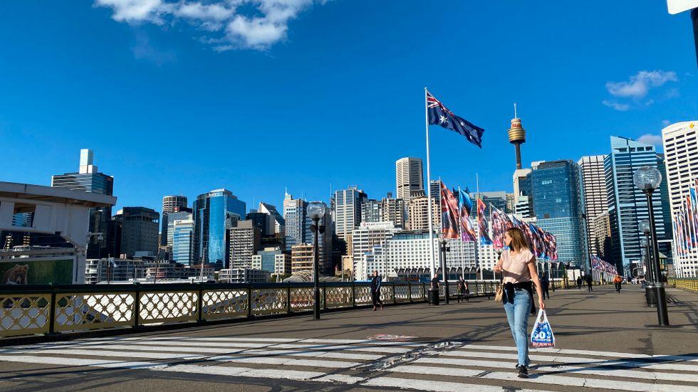 Några få människor är ute och rör på sig på gåbron Pyrmont Bridge i centrala Sydney, som är nedstängt till följd av coronasmittan. Arkivbild.