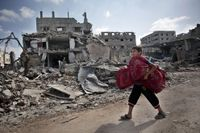 En palestinsk pojke bär på kuddar när han passerar ett förstört hus i Gaza under vapenvilan den 26 juli.