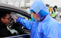 Kontrollant tar temperaturen på resenärer på väg in i Wenling i Kina i ett försök att hejda spridningen av coronaviruset.