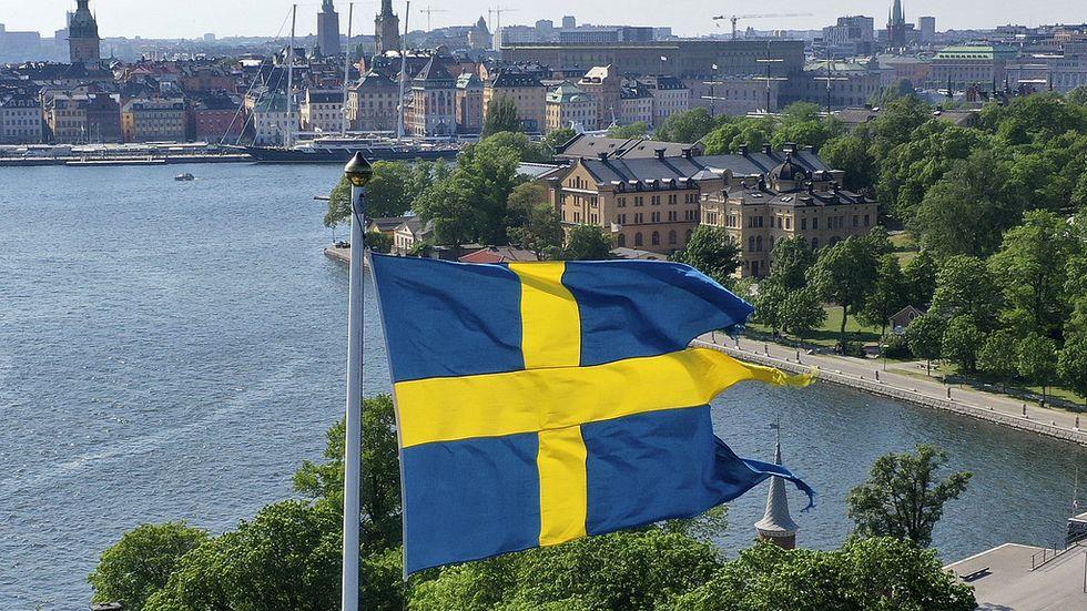 Svenska flaggan vajar på kastellet på Kastellholmen med Skeppsholmen och Stockholm i bakgrunden.